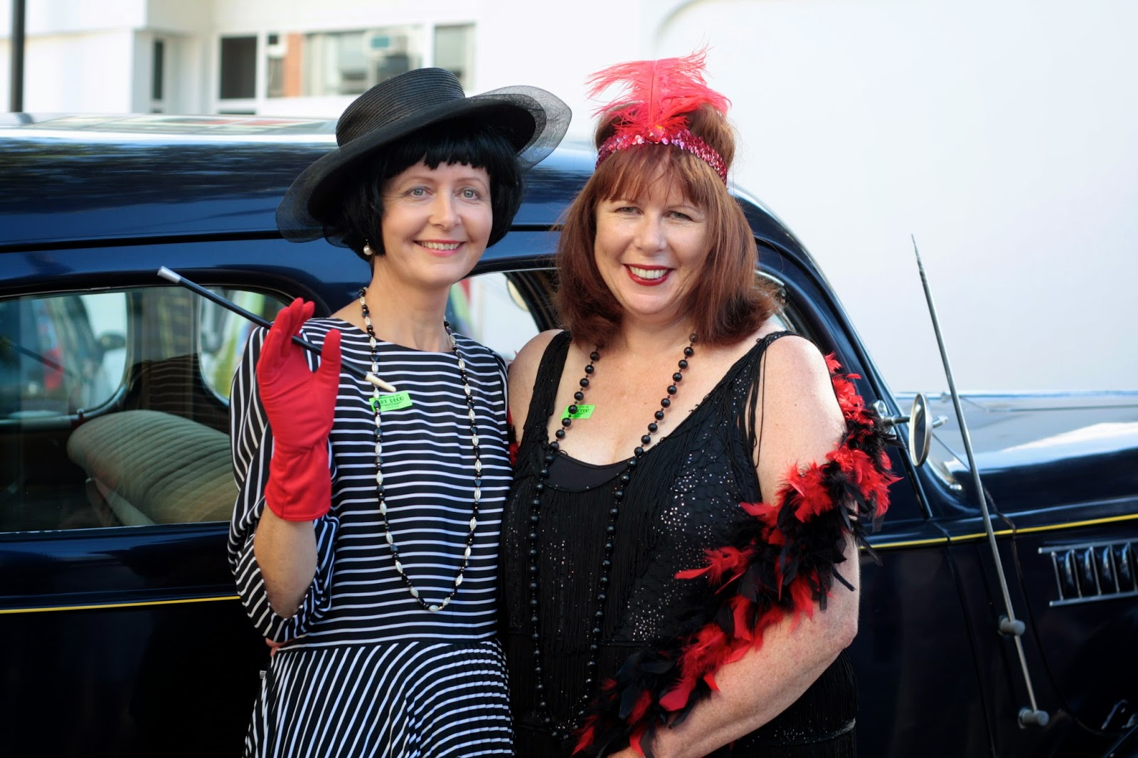 Two women in art deco flapper costume pose in front of a vintage car. One has a cigarette holder.