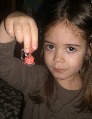 Four year old girl with Kinder Surprise toy sand timer.