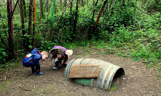 two children peering into a hobbit house