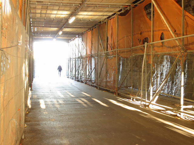 Partial silhouette of human entering a tunnel with orange shrouded scaffolding and wooden false wood.