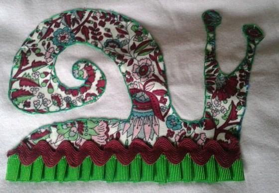 Detalle de caracol hecho a mano con telas para camiseta de niña
