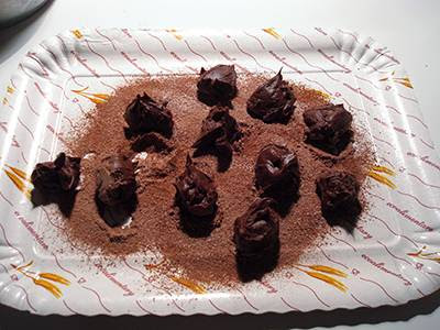 Tartufi al cioccolato: formare delle palline di crema e cospargerle di cacao