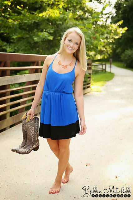 teen girl in blue dress holding cowboy boots on bridge