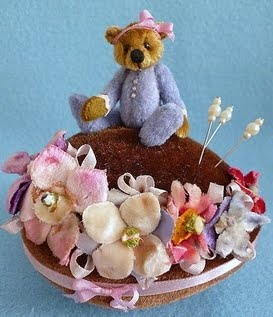 Lillia is sitting on an Easter Egg pin cushion. Trimmed with vintage flowers from an old hat.