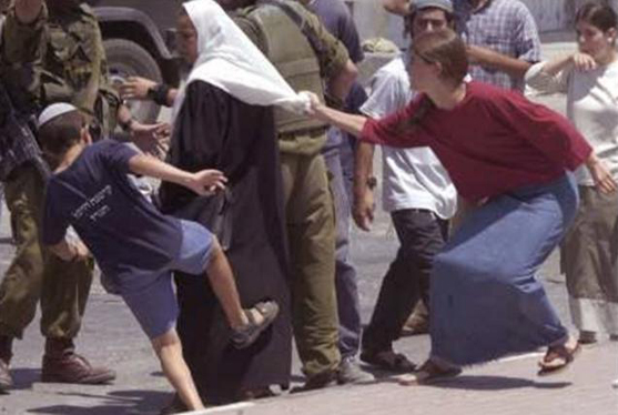 "A Palestinian woman is attacked by Israeli ""settlers."""