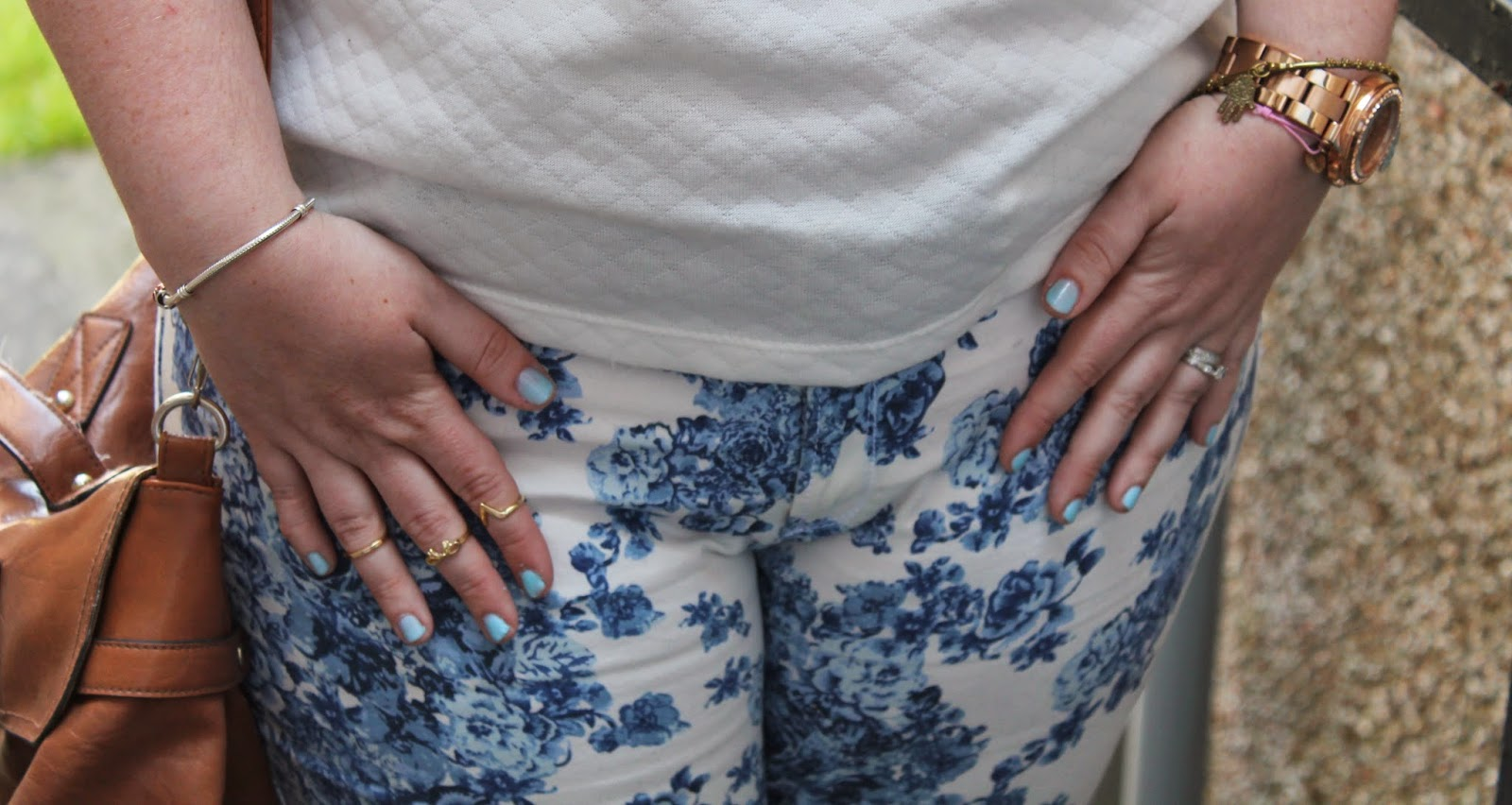 girl wears white jeans with blue floral pattern & knuckle rings