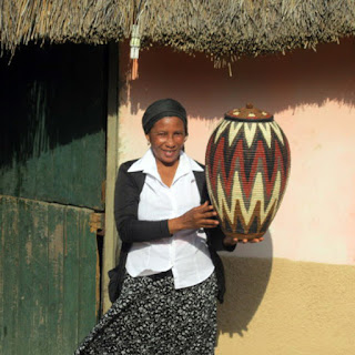 Zulu weaver at her home holds a Ukhamba basket she created.