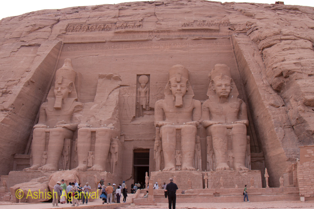 The statues outside the entrance to the Abu Simbel temple with tourists at the base