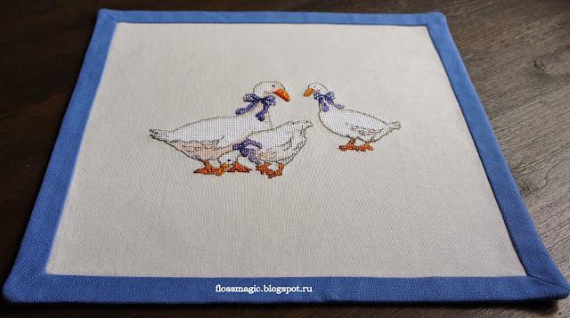 вышитая крестиком салфетка с изображением гусей