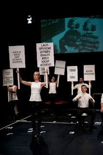 "Five people on stage wearing white T-shirts and black pants holding signs with slogans in the air: ""I'M DEAF. I DON'T UNDERSTAND A SPEAKING TEACHER""; ""I'M NOT ALLOWED TO SIGN AT HOME EITHER""; ""LEARNING SPEECH DOESN'T MAKE ME HEARING""; ""1880-1981""; ""PATERNALISM""; ""ADAPTION""). Behind them picture a photograph is projected showing two young boys – hands folded on their back and wearing headphones – from behind."