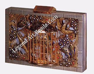 An openwork vanity case in gold and silver; the decoration of birds and a cage is applied with enamel and set with rose diamonds (1945)