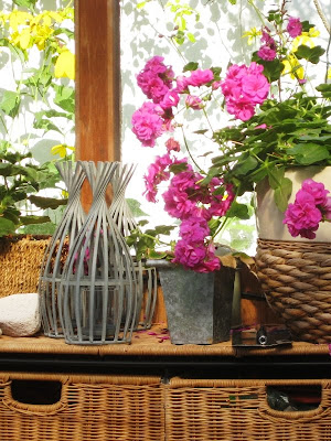 Pink flowers on a bright shelf with ornaments and wicker baskets