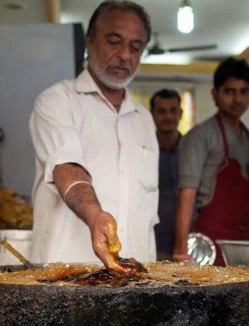 Cozinheiro Indiano frita peixe com as próprias mãos, sem usar frigideira