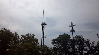 a couple of cell phone towers one with a spire