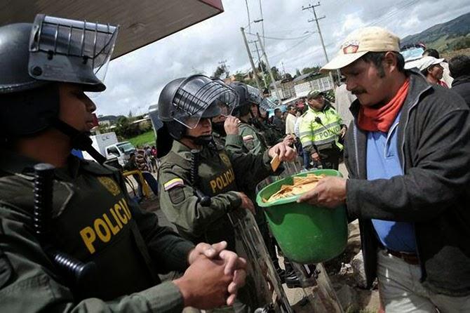 Демонстранты делятся крекерами с колумбийскими полицейскими во время акции протеста в Колумбии в 2013 году.