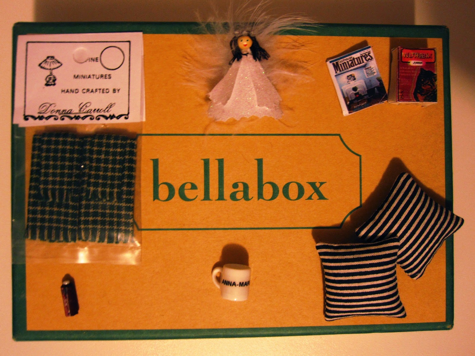 Selection of dolls house miniatures displayed on the top of a small cardboard box labelled 'bellabox'