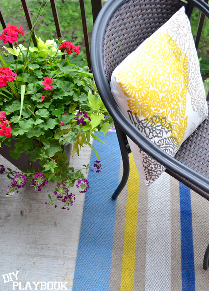 My yellow pillow and flower pot look great next to the DIY painted rug.