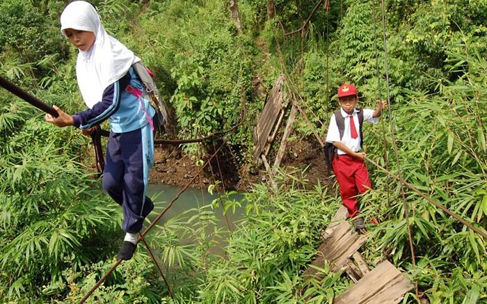 Each day 20 determined pupils have to cross the local river like circus performers after the suspension bridge collapsed in heavy rain.Picture: Panjalu Images / Barcroft Media