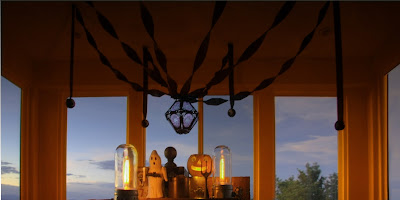 Sunset photo of A vintage-style table setting of black crepe paper with a Bindlegrim lantern, also with refurbished lighting, wooden boxes, vintage pumpkin, and paper mache ghost by Hobgoblin