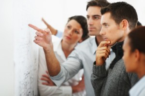 Photo image of team of knowledge workers analyzing a problem on a whiteboard.