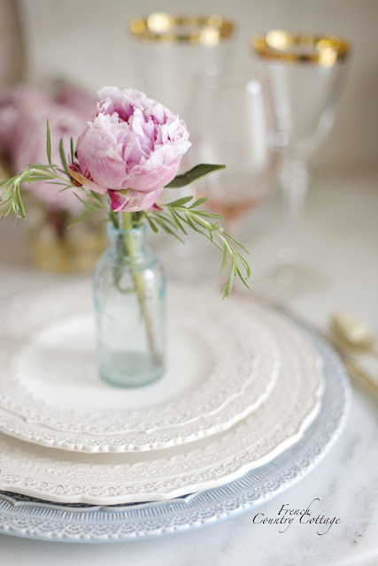 Peony and rosemary in small bottle on plates
