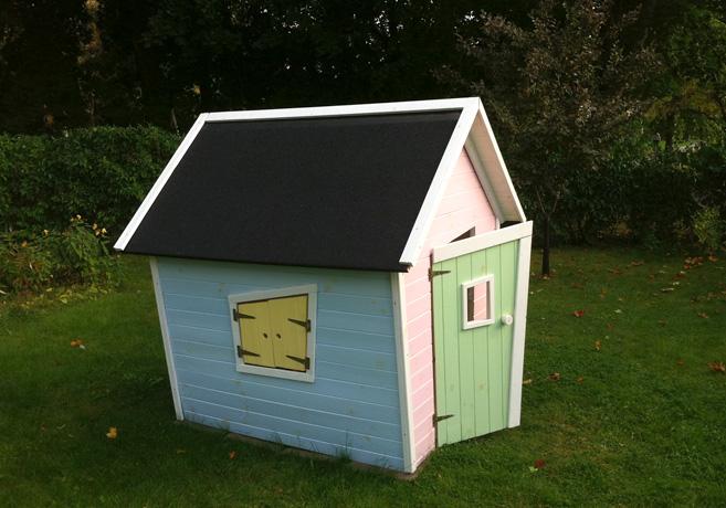 En lekstuga med ljusblå långsida, gula fönsterluckor och rosa framsida.