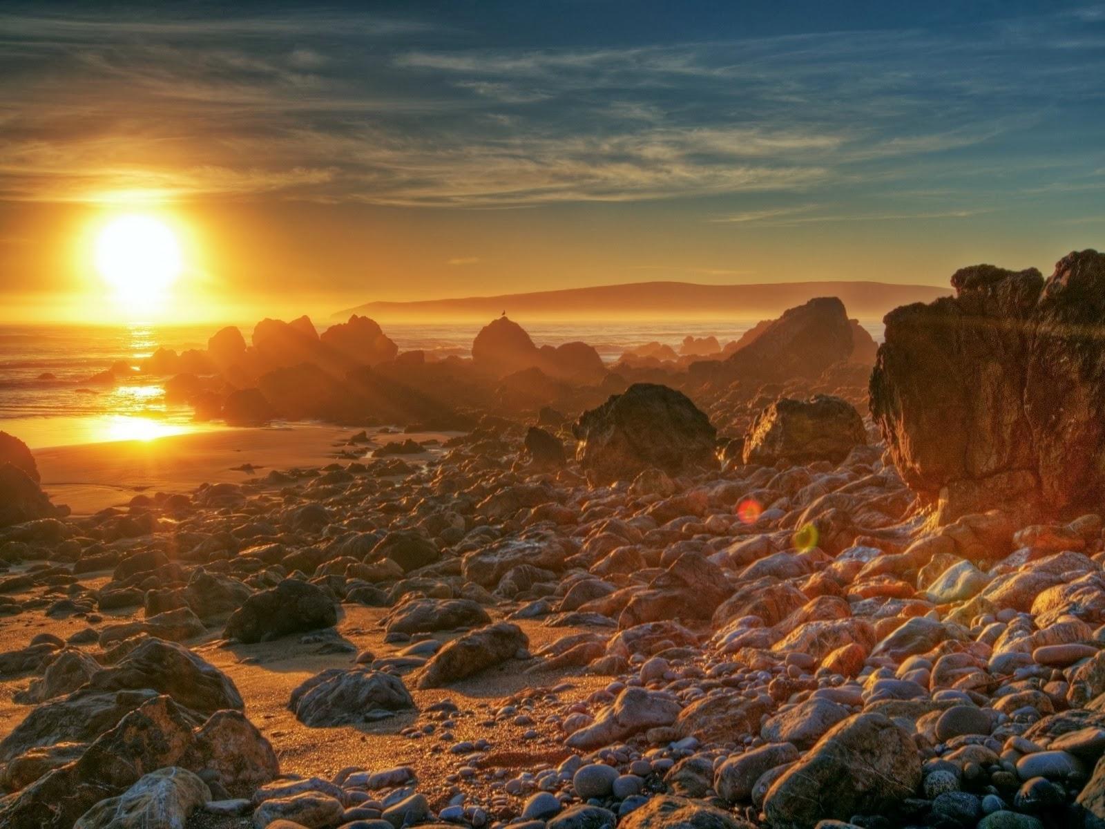 Puesta de sol, con rocas en la costa