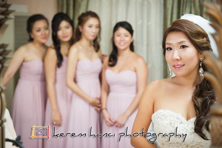 Ellie is ready for the ceremony while her bridesmaids are admiring her in this shot through the mirror.