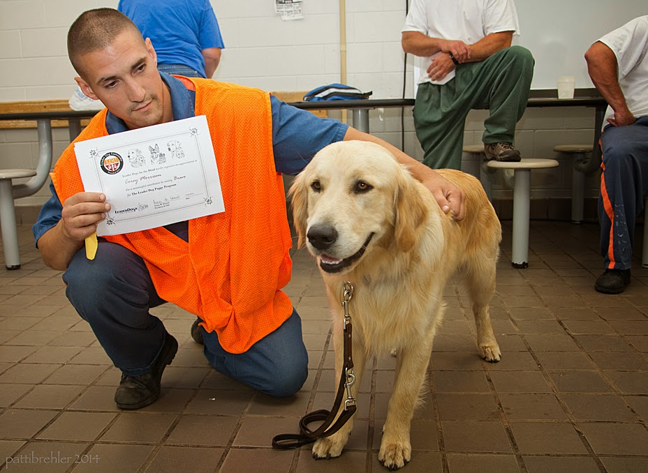 A man wearing blue prison pants and shirt with an orange vest is kneeling on his left knee next to a golden retriever, who is standing, looking toward the camera. The man is looking at the dog, with his left arm draped over the back of the dog, and holding up a certificate with his right hand. There are two men and a woman in the background.
