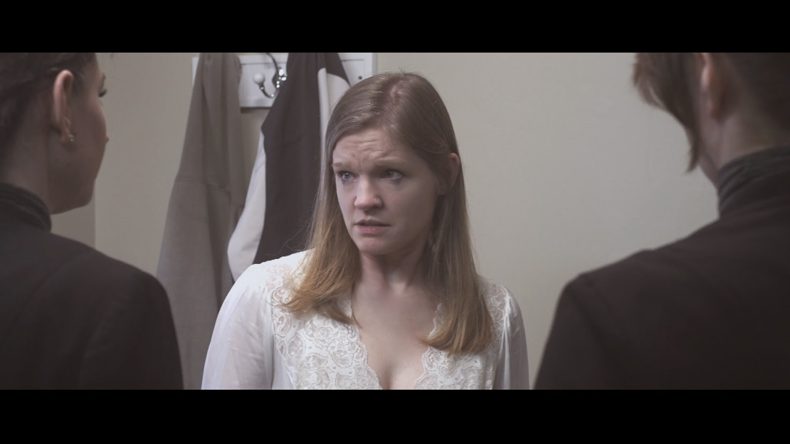 Gloria (Julie Atkins) looks worried when two Collection Agents enter her home.