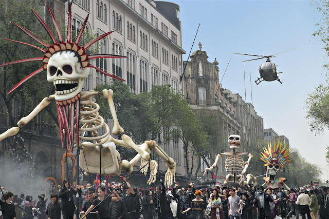 Bond chases Sciarra through the Day of the Dead parade in Mexico City. Sciarra's helicopter swoops in to collect him in Metro-Goldwyn-Mayer Pictures/Columbia Pictures/EON Productions' action adventure SPECTRE