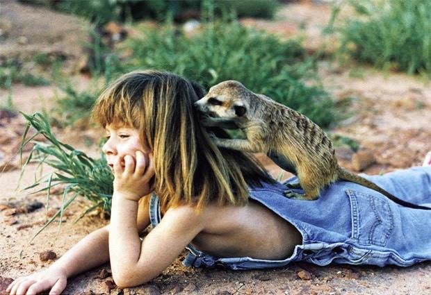 La niña tarzán con un animal jugando con su pelo