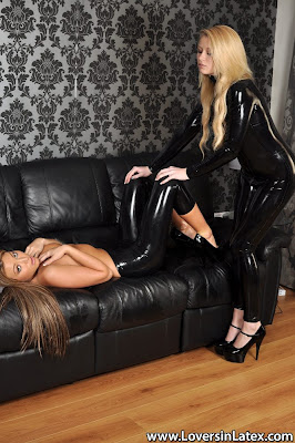 Lesbian Latex Slave Held by her mistress on Black Leather Sofa