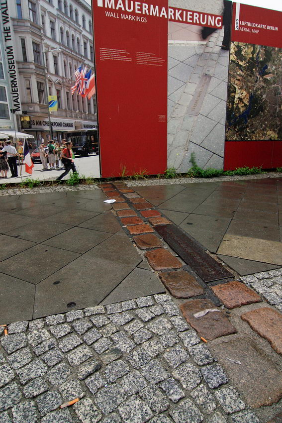 Pormenor do passeio onde existiu o muro a atravessar o passeio. Ao fundo painéis com cartazes alusivos ao muro e mais ao fundo, rua pedonal com prédios e algumas pessoas
