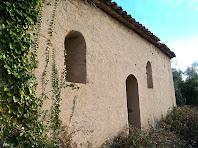 Detall de la façana de migdia, amb la porta i dues finestres, on podem apreciar l'arrebossat que ha tapat tota la factura romànica