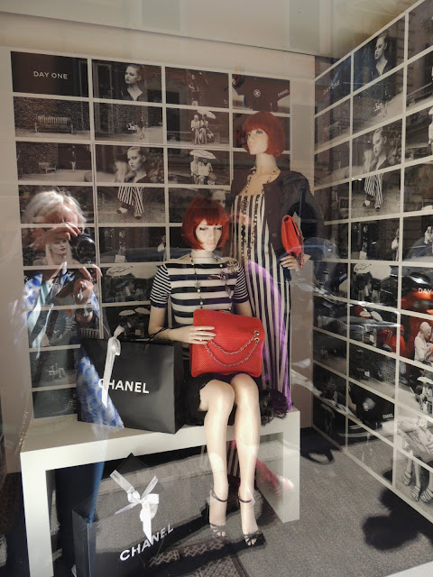 Chanel window display with red bob wigs and black and white photos