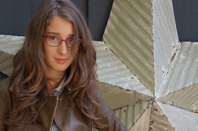 natural hair, industrial star, glasses, olive brown leather jacket, light was denim top.