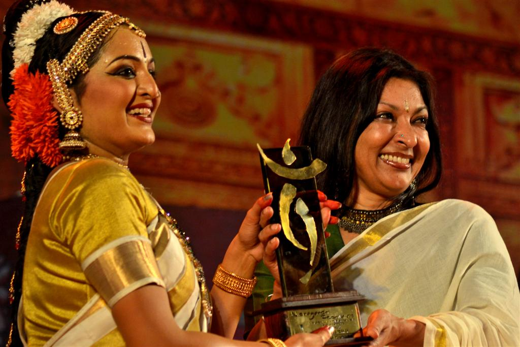 Manju Warrier is receiving memento from Mallika Sarabhai