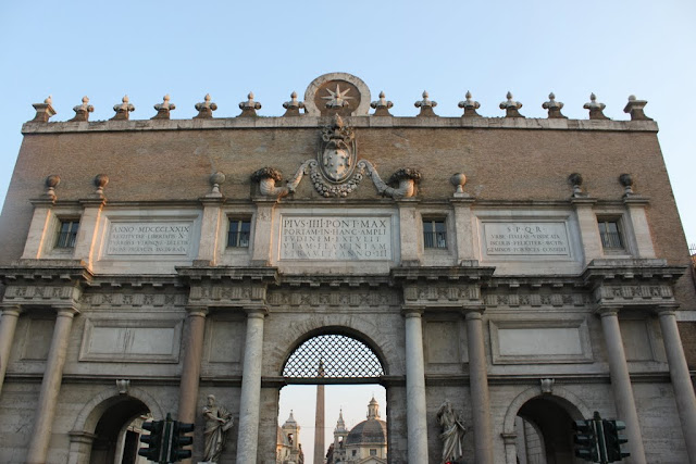 The main gate of Porta del Popolo from the busy streets in Rome, Italy