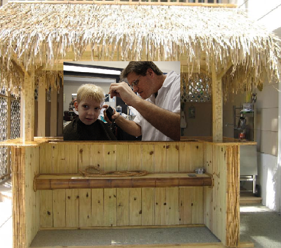 A barber cutting hair in a tiki bar. Tiki Barber