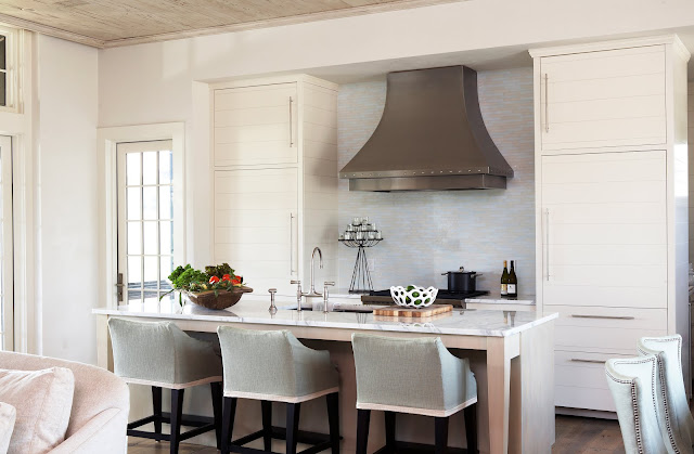 kitchen in a beach house with white cabinets, an island with marble countertop, and small subway tile backsplash