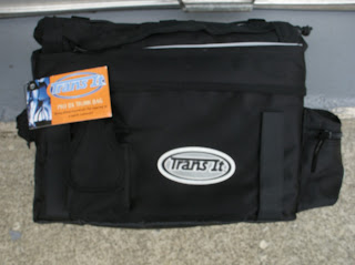 Black squarish bag that seems to be made of nylon canvas with various closeable pouches and pockets, as well as straps on it, and a zippered top. An oval patch that says Trans-It is on the front, and the manufacturer's tag is still attached.