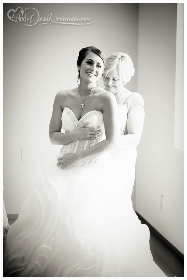 Mom helping daughter into wedding gown