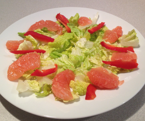 Image of a bed of romaine lettuce with peppers and grapefruit. Ready for the Jalpeno Shrimp