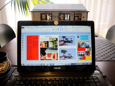 Laptop computer showing a magazine design in progress, on a dining table. AT the other end of the table is a dolls' house miniature school building.