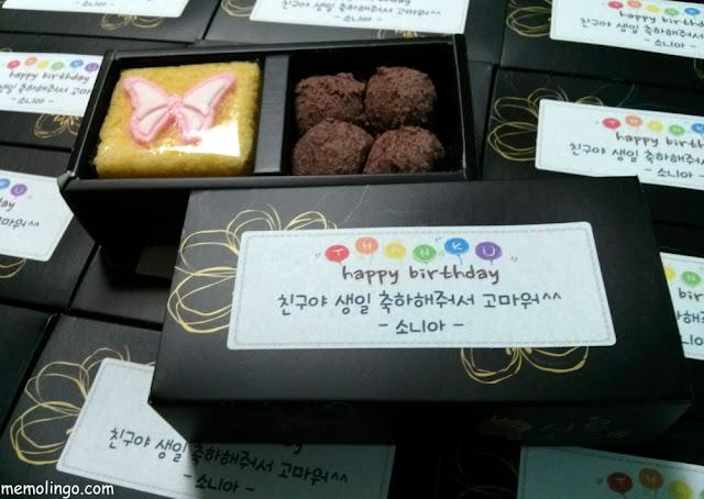 Cajita de cumpleaños con tteok y un mensaje en coreano