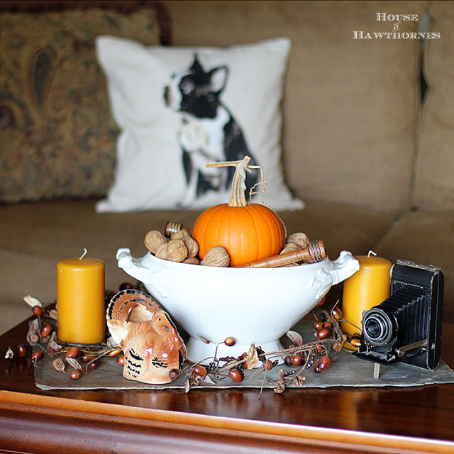 Thanksgiving table decor using vintage turkey planter, vintage camera and an urn full of nuts and pumpkins