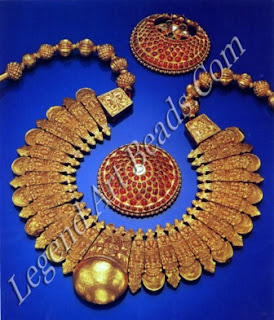 """Oblong gold lac-filled repousse pendants depicting the goddess Lakshmi and demon face motifs, with alternate crescent and palmette-shaped terminals; the large central boss-shaped tali emblem surmounted with an image of the goddess Gaialakshmi flanked by elephants is inscribed: """"Captured from a Singh Sindan, at the Battle of Sabraon on the 106 of February 1845, by Robert Henry Hastings of the 59' Native Infantry."""" The two hair ornaments set with cabuchon rubies symbolize the sun and the moon."""