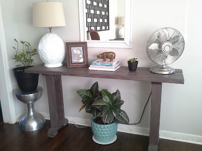 console table styling, west elm brass rhino, plants, metal fan, pineapple lamp, stacked books bamboo mirror, rustic console table