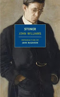 Image: the cover of Stoner. The cover is a painting of a middle-aged man, thin, with brown hair and glasses, who has his hands in the pockets of his black overcoat and is looking down. The title and author are in a blue box in the middle of the cover.